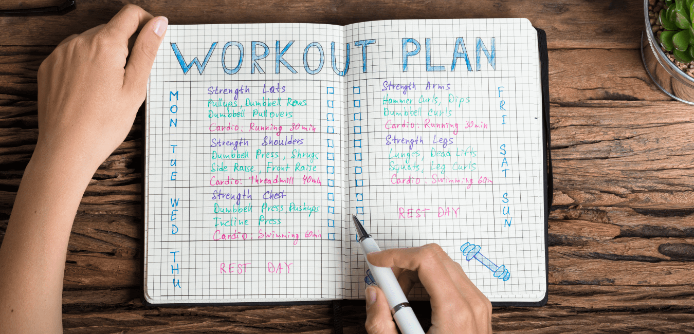 How to make a workout plan. Woman's hands drawing up a workout plan in a colorful journal.