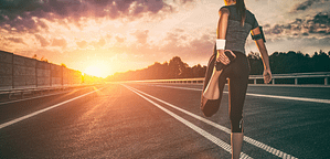 A Workout Plan You Can Stick to. Woman standing on a road stretching her quads getting ready for a run looking at a sunset.
