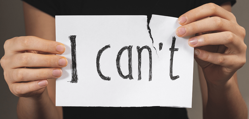"Realizing you can do what you want to achieve. Woman's hands holding a sign that says ""I can't"" and tearing off the 't'."