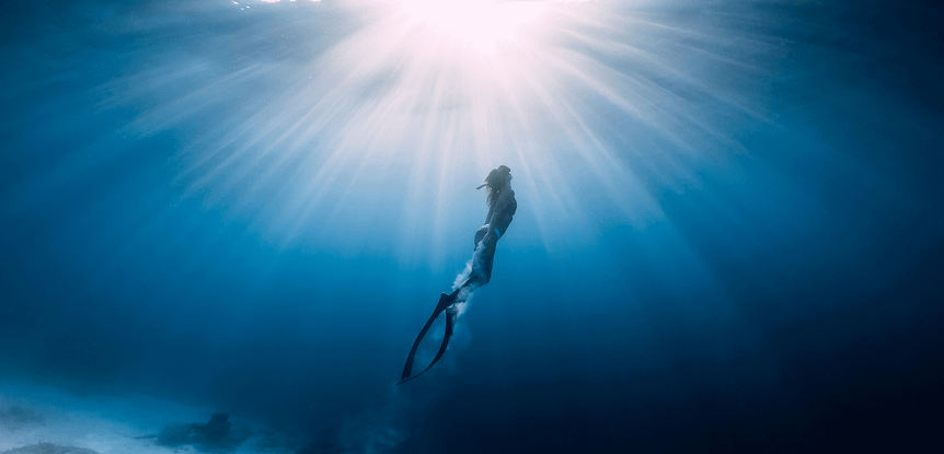 Pushing Limits Freediving: Interview with Katie Coeckelenbergh-Sawyer woman freediving in blue water swimming towards surface, sun overhead