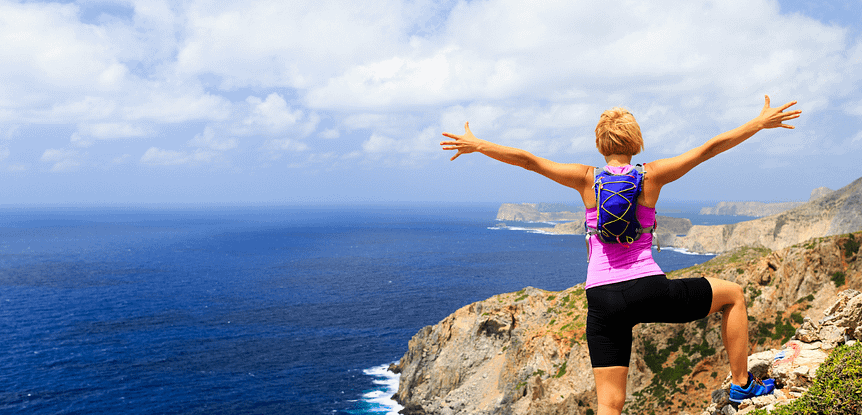 What Goals Should I Set and how do I achieve them? Woman with pink shirt and purple daypack standing on mountain overlooking ocean with arms stretched to sky.