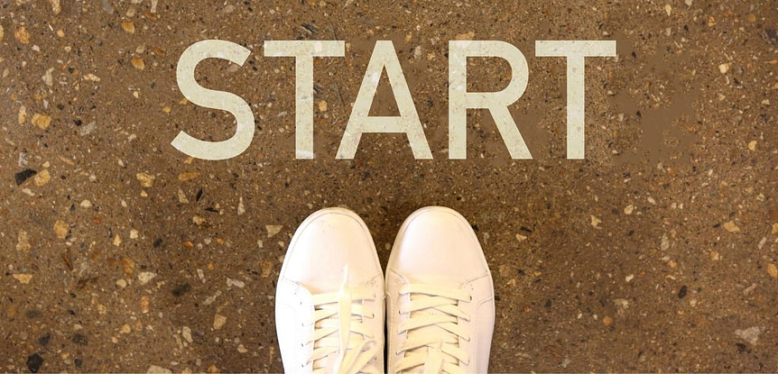 "Always starting over. Looking down onto two white sneakers with the word ""START"" above them."
