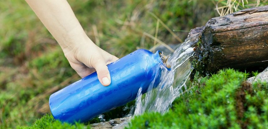 Best hydration bladder and hiking tips. Woman holding blue water bottle under flowing water during a hike.