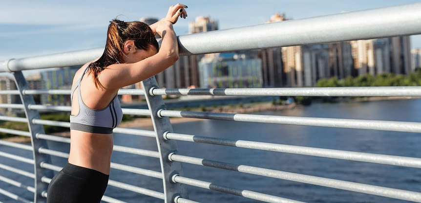 3 Signs Working Out is Boring You, and What You Can Do To Fix It. Woman in workout gear leaning head against metal fence.