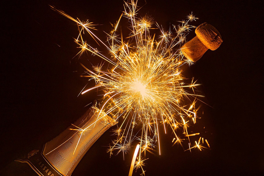 fitness resolutions for the new year. Dark background, gold champagne bottle bursting open with sparkler.