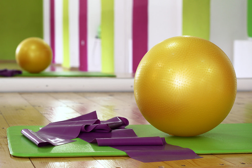 Indoor home workout equipment. Resistance band and exercise ball on green yoga mat in an exercise studio.