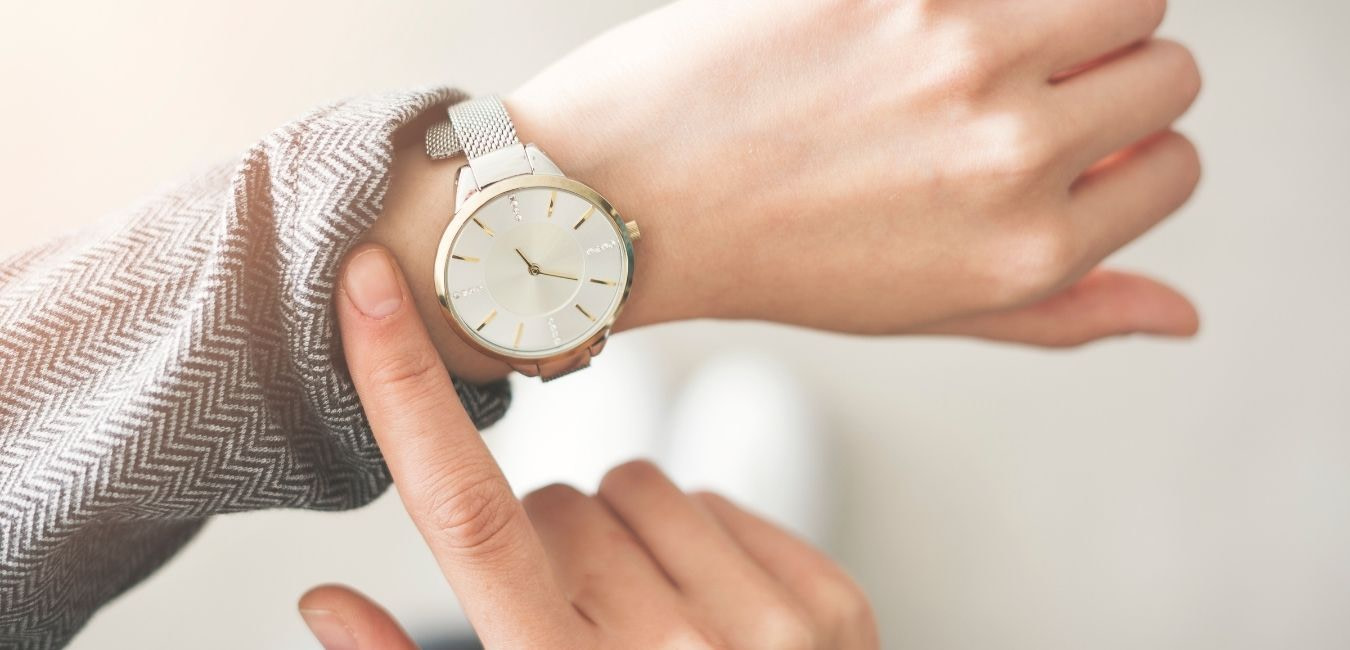 Finding time to exercise. Woman pulling up sleeve of her gray sweater to check the time on her wrist watch.