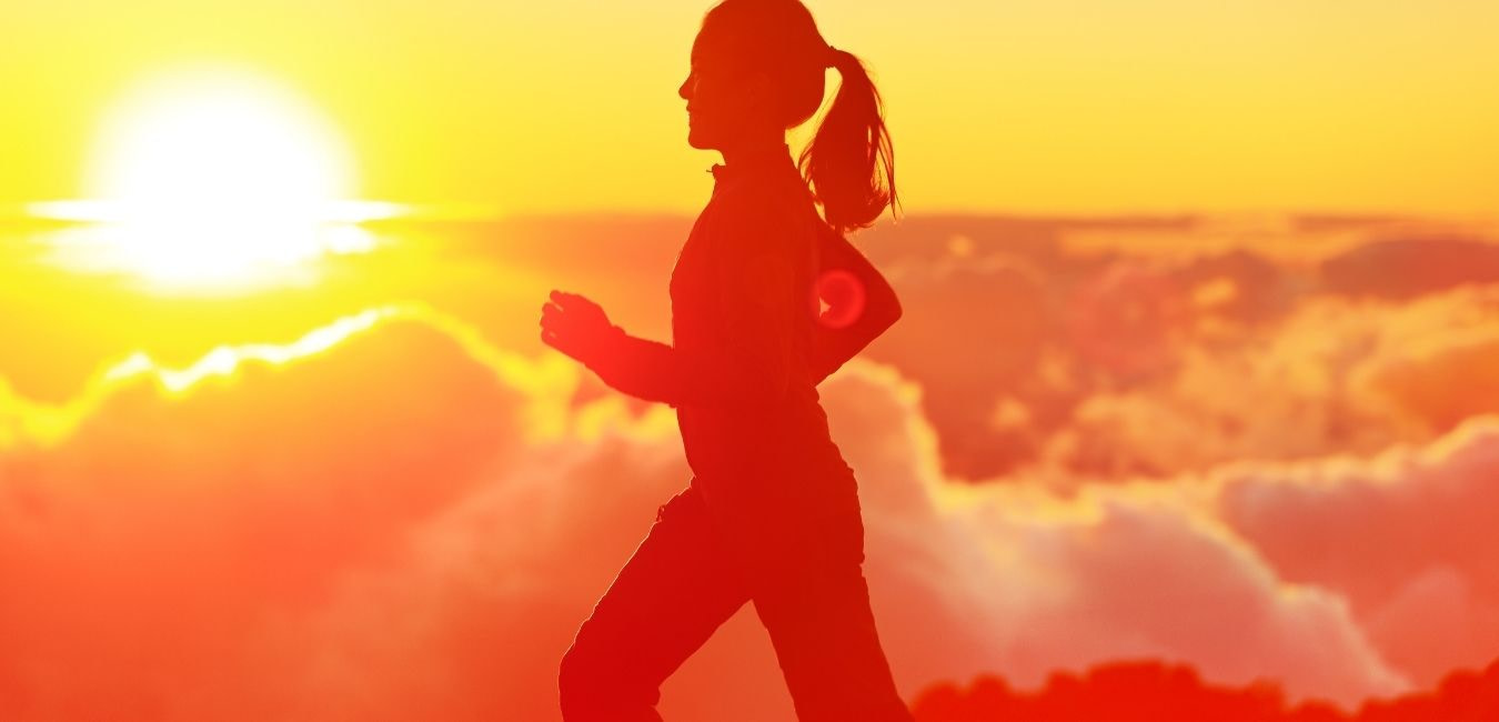 Hand weight exercises. Silhouette of a woman walking with sun and clouds in the background.