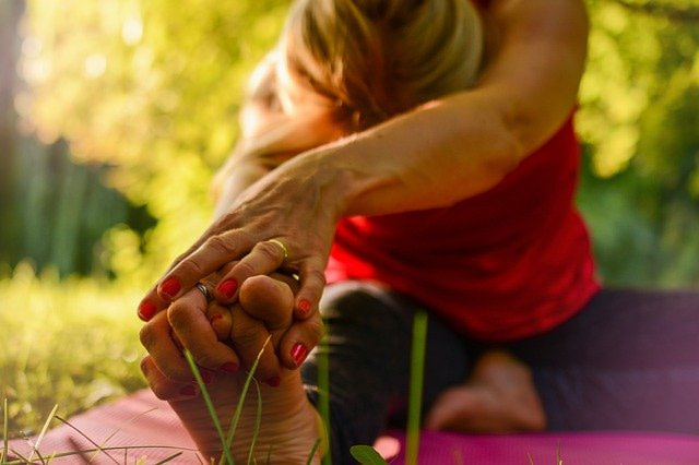 Why Stretching is Important. Woman in red tank top stretching outdoors.
